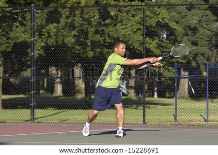 A man is outside on a tennis court playing tennis.  He is looking at the tennis ball after he just hit it with his racket.  Horizontally framed shot.