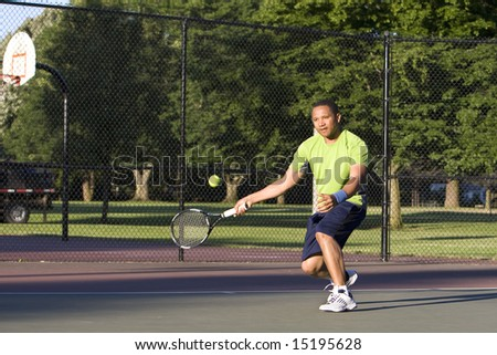 A man is outside on a tennis court playing tennis.  He is looking at the tennis ball.  Horizontally framed shot. - stock photo