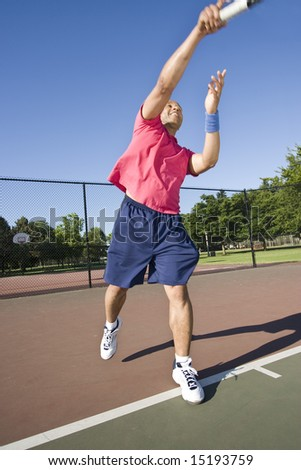 A man is outside on a tennis court playing tennis.  He is reaching up to hit the ball and looking at his racket.  Vertically framed shot.