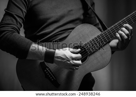 A man is playing on acoustic parlour guitar