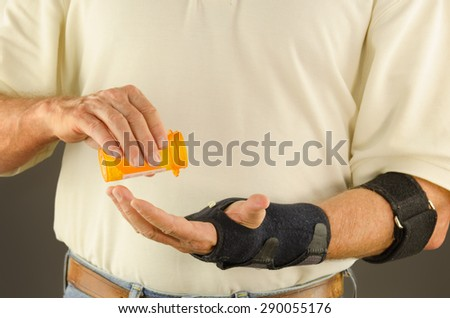 A man is pouring medication into his hand for pain, anti-inflammatory. tendinitis, tennis elbow and carpal tunnel and the man has a brace on his wrist and a tendon strap on his forearm. - stock photo