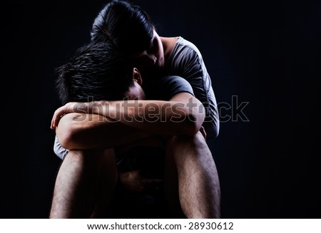 A man is sad and being consoled/embraced by his partner - stock photo