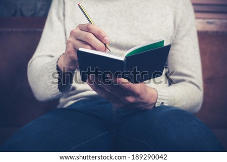 A man is sitting on a sofa and writing notes in a notebook - stock photo