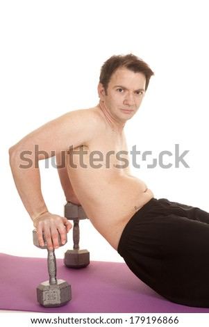 A man is sitting on weights working out. - stock photo
