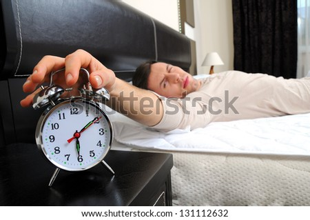 A man is sleeping with an alarm clock in front - stock photo