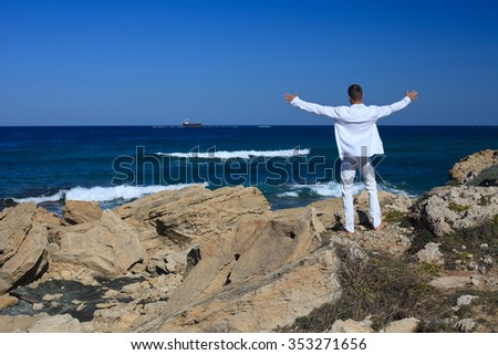A man is standing arms spread on a rock near the sea  - stock photo