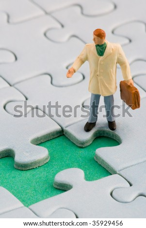A man is standing in front of a missing jigsaw puzzle piece - stock photo