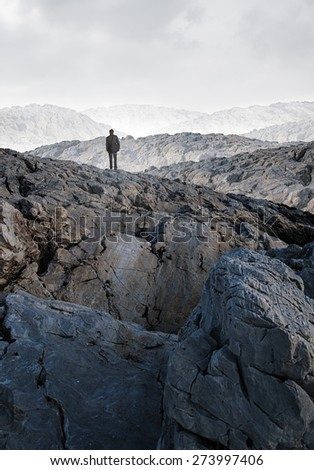 A man is standing in the mountains - stock photo