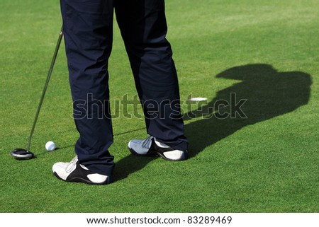 A man is standing on the green of a golf course. He is putting the ball into the hole. - stock photo