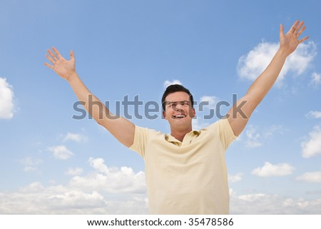 A man is standing outside with outstretched arms.  He is smiling and looking away from the camera.  Horizontally framed shot. - stock photo