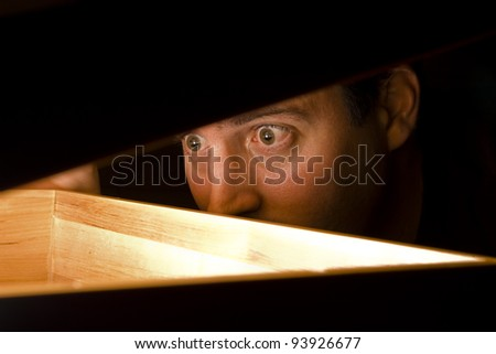 A man is surprised by what he finds in a box - stock photo