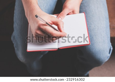 A man is taking notes in a notebook - stock photo