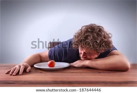 A man is thinging if he should eat the apple. Picture is toned in a dodge and burn effect. - stock photo