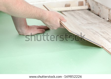 A man is trying to fit a piece of laminate to an other one. - stock photo