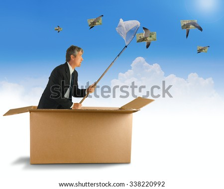 A man is trying to net the money that is flying by on the wings of birds as he is coming out of a box representing thinking outside the box and creative business strategy ideas - stock photo