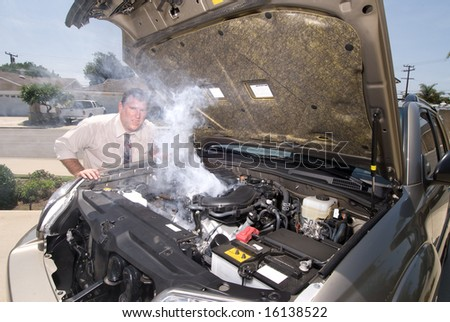 A man is very frustrated and sweaty while trying to evaluate his smoking car engine. - stock photo