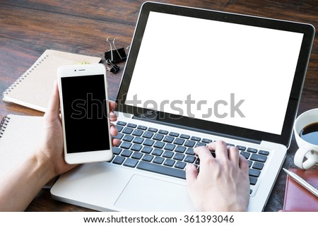 A man is working by using a laptop computer and a smartphone on vintage wooden table.  - stock photo