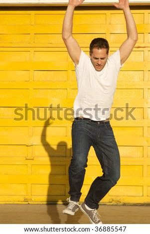 A man jumping off with shadow behind him - stock photo