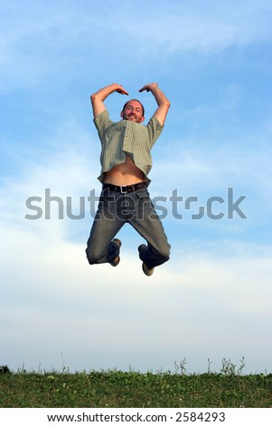 A man jumping over grass with a blue sky behind him - stock photo