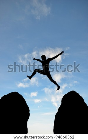a man jumps from one rock to another - stock photo