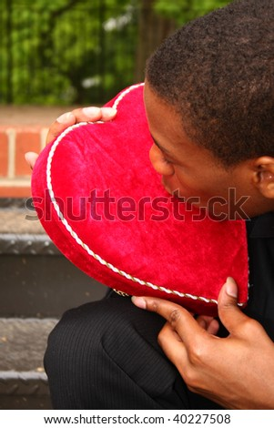 a man kissing a heart shaped box
