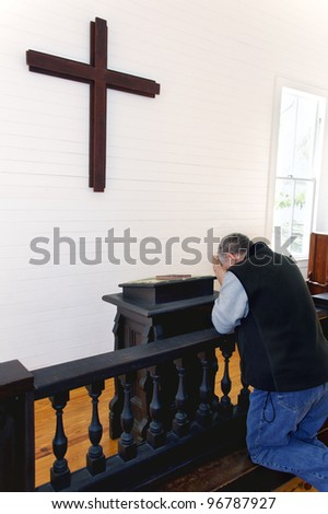 A man kneeling and praying at a church in front of a wooden cross. - stock photo