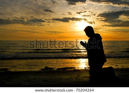 A man kneeling and praying at the ocean with his head bowed. - stock photo