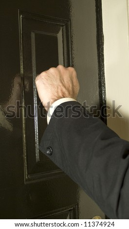A man knocking on a newly painted shinny door with his fist.