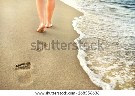 A man leaves footprints in the sand - stock photo