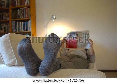 A man lies on the couch with his feet up, reading the paper. Focus on the slightly worn socks. Space for text on the wall, top right. - stock photo
