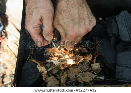 A man lights a fire with a flint. Coal, bright sparkles with smoky tails, dry leaves and twigs. - stock photo