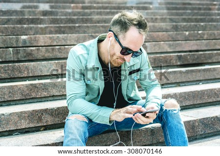 A Man listening to the music with earbuds from a smart phone  - stock photo