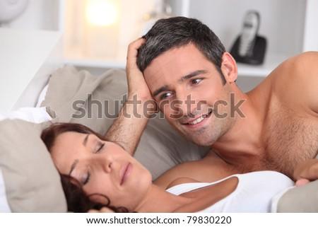 a man looking a wife sleeping deeply - stock photo