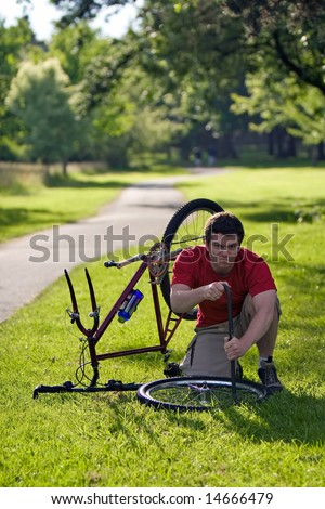 A man looking angry, uses a crowbar, to take the tire off the rim of his bicycle. - vertically framed