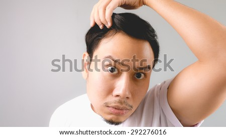 A man looking at the mirror and shocked that he is losing his hair. An asian man with white t-shirt and grey background. - stock photo