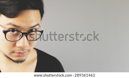 A man looking at you under eyeglasses.