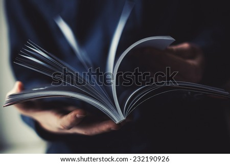 A man looks at a magazine. Press hands. - stock photo
