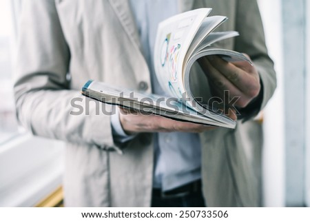 A man looks at a magazine. Press hands.