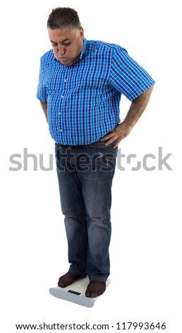A man looks at the scale concerned about his weight, full length - stock photo