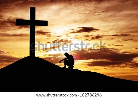 A man making a confession to the cross, shot under dawn sky