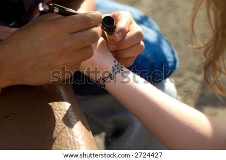 A man making temporary henna tattoo on woman's wirst - stock photo