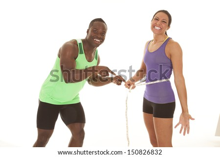 A man measuring a woman's belly with a smile on his face. - stock photo
