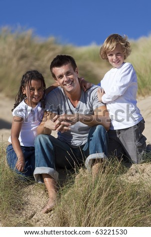 A man mixed race girl and young boy, father, son and daughter, sitting down and having fun in the sand dunes of a sunny beach