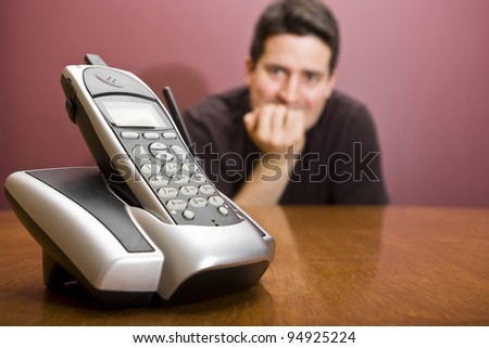A man nervously waits for the phone to ring - stock photo