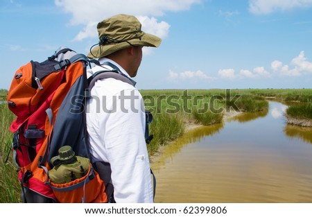 A man observing the wild landscape before him - water and sky - stock photo