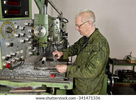 A man of retirement age runs a milling machine for metal