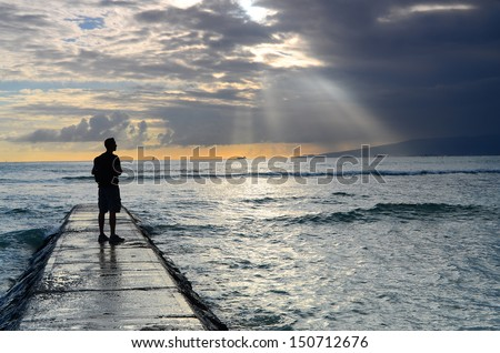 A man on a jetty silhouetted against the sun's rays and ocean. - stock photo