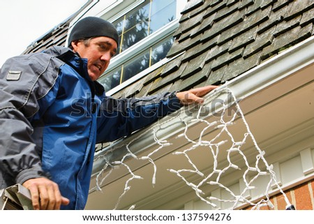 A man on a ladder putting up Christmas lights on the house - stock photo