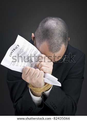 A man on a suit holds a contract on his tied hands. - stock photo