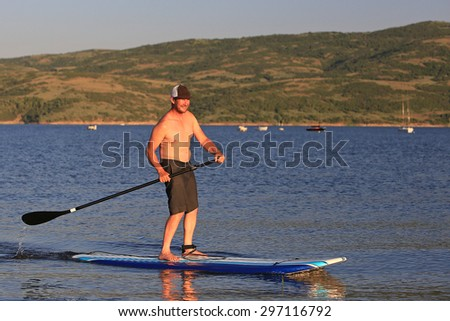 A man on a SUP or stand up paddle board in a lake, Utah, USA. - stock photo